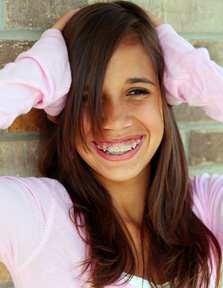 teen with braces pink shirt